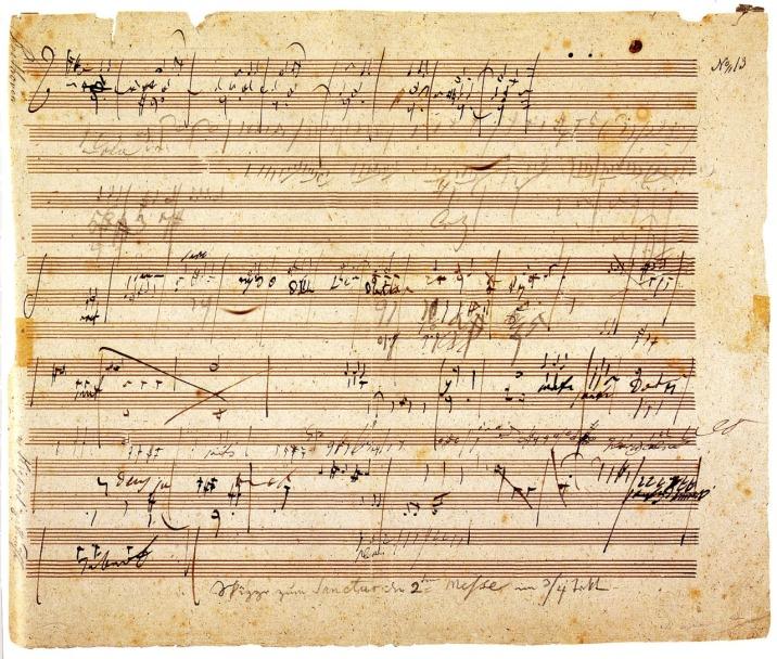 """Autografo di Ludwig van Beethoven (1770-1827) per la Missa Solemnis (1820-1). A matita e penna, su questo foglio, che Beethoven aveva strappato dal quaderno e portava in tasca, ci sono appunti per le sezioni del Sanctus, del Benedictus e del Gloria. È proprio con il Benedictus della Missa Solemnis che Huxley accompagna il proprio saggio """"Music at Night"""": """"'Benedictus, benedictus...' One after another the voices take up the theme propounded by the orchestra and lovingly meditated through a long and exquisite solo (for blessedness reveals itself most often to the solitary spirit) by a single violin. 'Benedictus, benedictus...' And then, suddenly, the music dies; the flying djinn has been rebottled."""""""