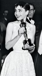 """Audrey Hepburn alla cerimonia di premiazione degli Academy Awards nel 1954, dove vinse come Miglior Attrice Protagonista per """"Vacanze Romane"""". Per l'occasione, l'attrice indossò un abito bianco a ricami floreali firmato Givenchy."""